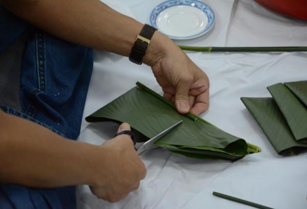Cach lam banh chung - rửa sạch lá dong và lau khô rồi gấp cắt lá chuẩn bị gói bánh chưng