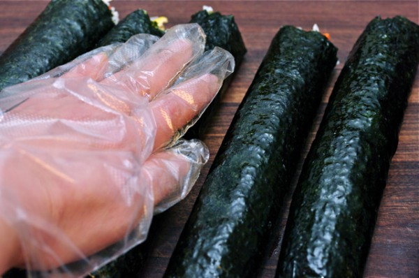 Cơm cuộn - xao dầu mè vào lòng bàn tay và xoa đều lên trên những miếng kimbap