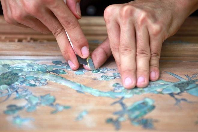 Người thợ dùng hai con dao để quét keo ở mặt gỗ lõm, rồi ấn những mảnh trai đã được cắt định hình âm xuống.
