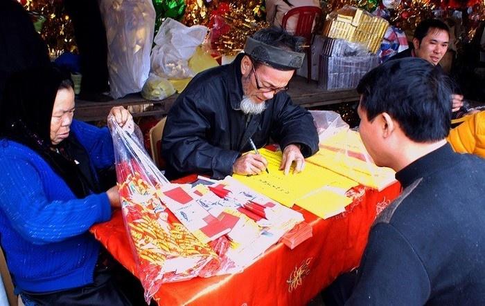 Ông đồ của chợ Viềng Nam Định đang cho chữ Nho tặng du khách ngày Tết