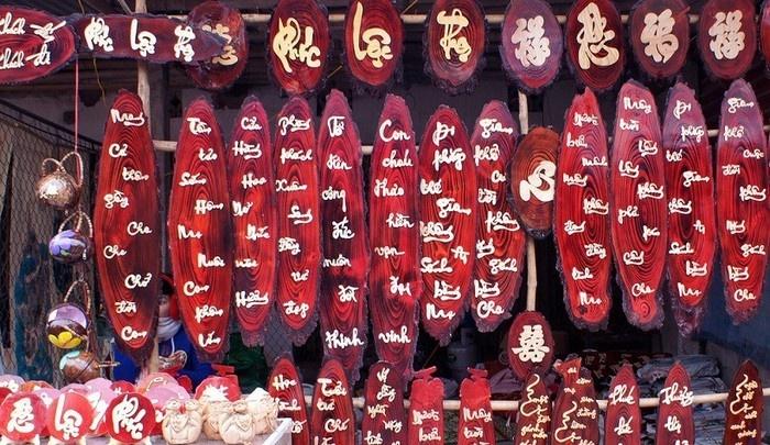 Sạp bán câu chúc Tết độc đáo trên gỗ nổi bật một góc chợ