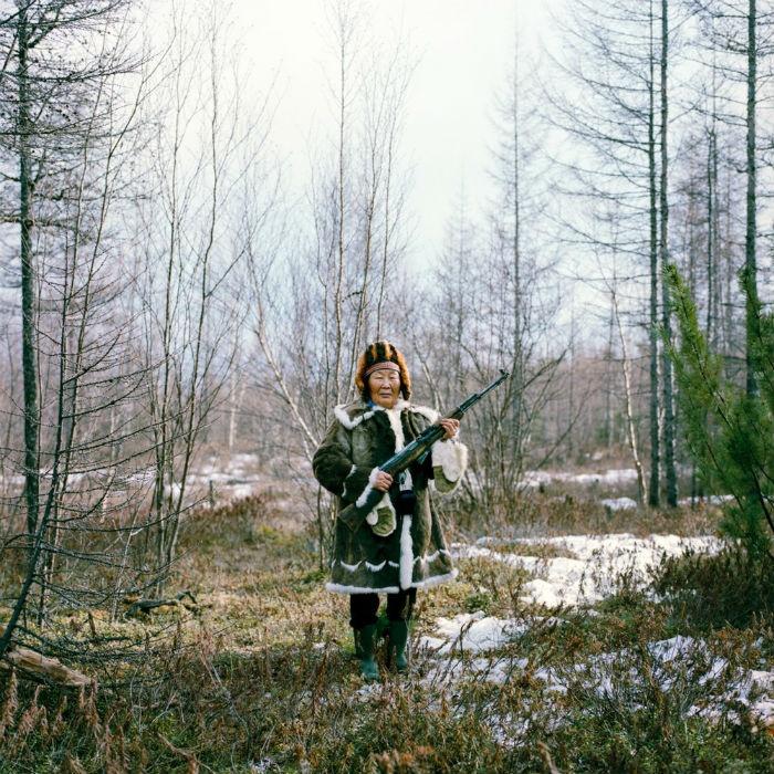 Bà Maria Ivanova đang mặc trang phục truyền thống của người Evenk, cầm trên tay khẩu súng trường khi tập bắn trong chuyến dã ngoại với gia đình.