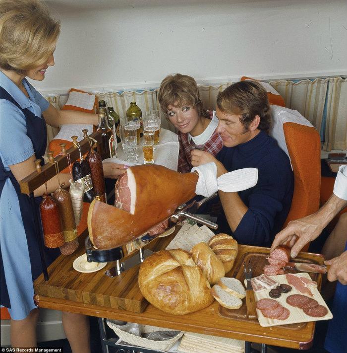 Trên khoang hạng nhất năm 1969, một nữ tiếp viên đang phục vụ thịt hun khói cắt salami và phi lê cá hồi.