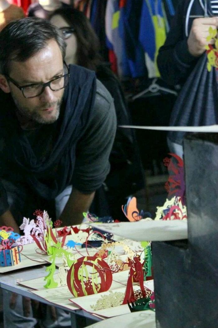 Một du khách chăm chú ngắm những tấm thiệp 3D Hà Nội sáng tạo.