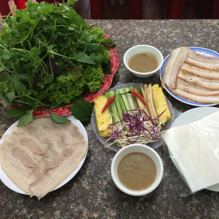 Món chính của quán là bánh tráng cuốn thịt heo với đĩa rau đầy ú ụ.