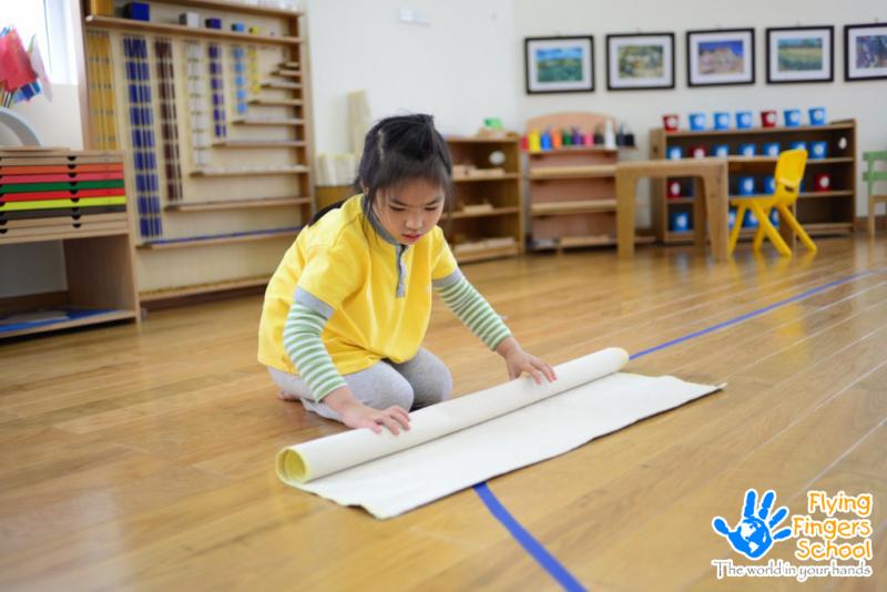 Trải và cuộn thảm giúp cho bé rèn luyện các đầu ngón tay linh hoạt.